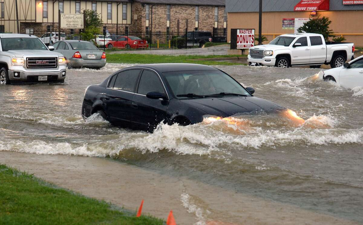 Cars push through high waters on Jimmy Johnson Boulevard in Port Arthur during Tuesday's rain. Several streets in southern Jefferson County were closed to prevent water from being pushed into homes. Photo taken Tuesday, 6/19/18