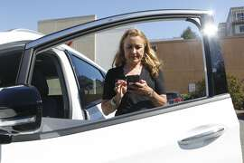 Esther M. de Frutos, an Uber driver of one year, checks her 4.96 review rating on the Uber app on Monday, June 18, 2018 in San Francisco, Calif.