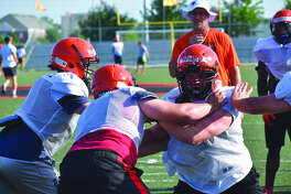 Edwardsville coach Matt Martin, back, watches his linemen during a drill on Tuesday inside the District 7 Sports Complex.