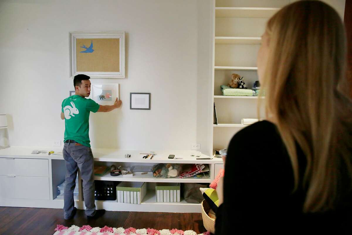 """Thai-can """"Paul"""" Nguyen (l to r), Taskrabbit tasker, consults with Lauren Fraser, San Francisco resident, while hanging picture frames in the baby's room as it is prepared for the babys arrival on Monday, February 29, 2016 in San Francisco, California."""
