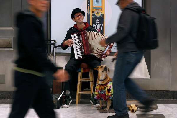 Robert Doerr plays an accordion with his dog Vera for commuters at the Civic Center BART station in San Francisco, Calif. on Tuesday, June 19, 2018. Doerr said he�s never seen the station so clean in the 10 years he�s been performing at the station after an increase of police patrols and continual maintenance and cleaning.