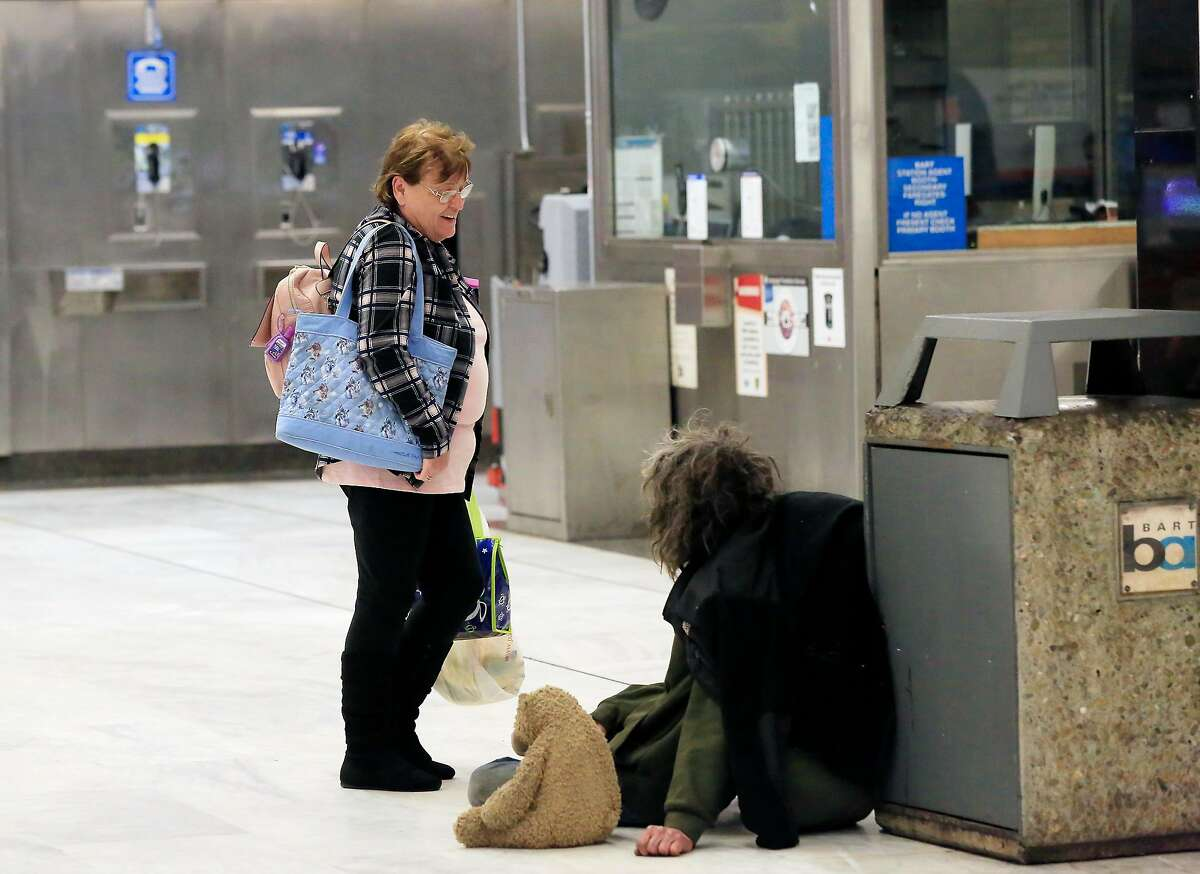 Kathleen Dumag (l to r) , of Brentwood, stops to talk with Casey Watson, who is homeless, as he sits on the ground at the Civic Center / UN Plaza Station on Friday, April 27, 2018 in San Francisco, Calif.