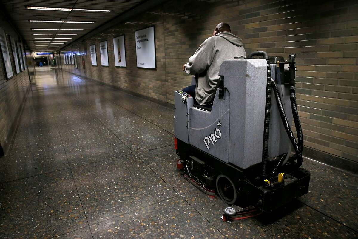 A maintenance worker cleans the floor of a corridor that was popular with IV drug users at the Civic Center BART station in San Francisco, Calif. on Tuesday, June 19, 2018. The station, long known for loitering and drug use, has seen significant change as a result of increased police patrols and continual cleaning.