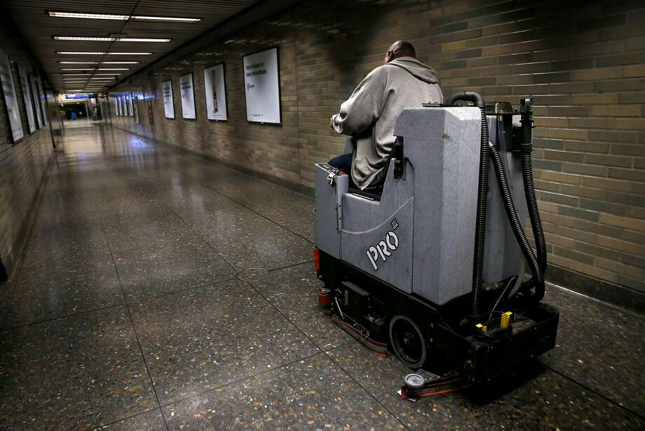 A maintenance worker cleans the floor of a corridor that was popular with IV drug users at the Civic Center BART station in San Francisco on Tuesday, June 19, 2018. The station, long known for loitering and drug use, has seen significant change as a result of increased police patrols and continual cleaning. Photo: Paul Chinn / The Chronicle