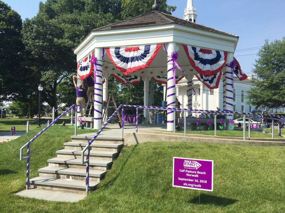 Volunteers help prepare the gazebo by placing purple ribbons on the supports and planting faux purple flowers around the structure on Monday, June 18. The spotlights around the gazebo have also been turned purple and will remain so through June 24 to increase awareness about Alzheimer's disease. Photo: Contributed Photo / Contributed Photo / Norwalk Hour contributed