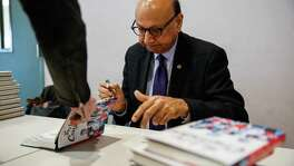 Khizr Khan, the Muslim-American Gold Star father who drew Donald Trump's ire two years ago, signs books in California. A reader likes his book on the Constitution, but says Congress has undone much of the founders' intent.