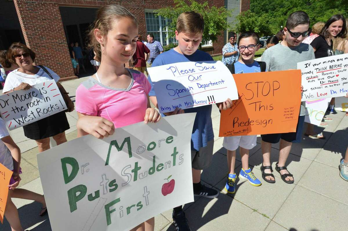 West Rocks Middle School 8th grader Autumn Anderson holds a sign as she stands with other students in support of their Principal Dr. Lynne Moore in front of City Hall on Tuesday June 19, 2018 in Norwalk Conn. More than one hundred people rallied and praised Moore in response to talks about removing her from West Rocks school