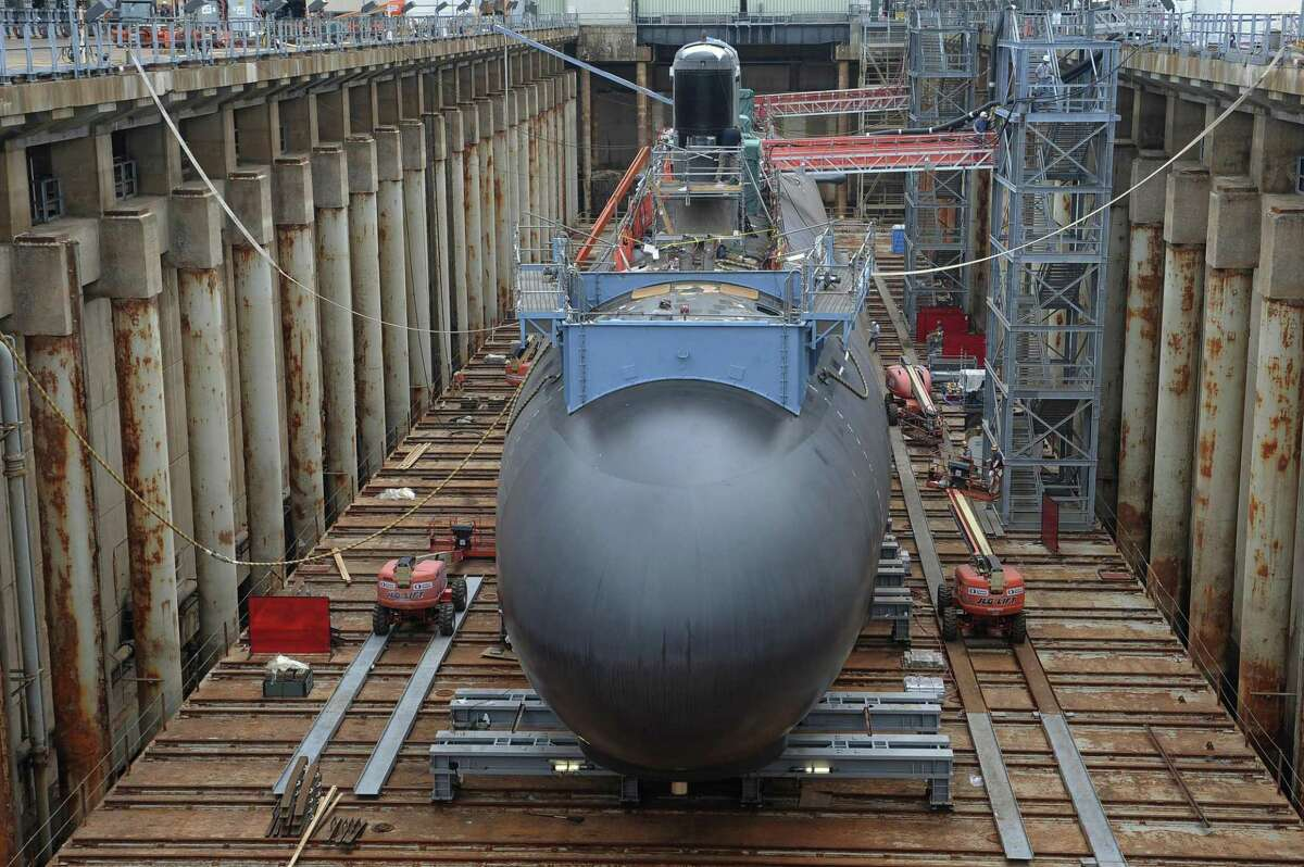 In this Thursday, July 30, 2015 photo, shipyard workers at General Dynamics Electric Boat prepare the submarine Illinois for float-off in Groton.