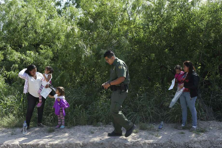 Supervisory agent Christian Alvarez gathers information from Honduran families who surrendered to the U.S. Border Patrol after crossing into the U.S. from Mexico in Mission on May 10. Photo: Jerry Lara /San Antonio Express-News / San Antonio Express-News