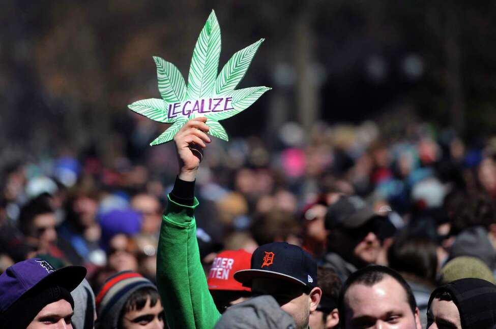 FILE - In this April 5, 2014, file photo, a man holds up a sign advocating the legalization of marijuana at the 43rd annual Hash Bash on the University of Michigan Diag in Ann Arbor, Mich. Michigan voters will decide whether to legalize the recreational use of marijuana. A citizen-initiated measure wasn't approved by the Republican-controlled Legislature before a 40-day deadline passed Tuesday, June 5, 2018. That means the ballot initiative will get a public vote in November. (Brianne Bowen/Ann Arbor News via AP, File)
