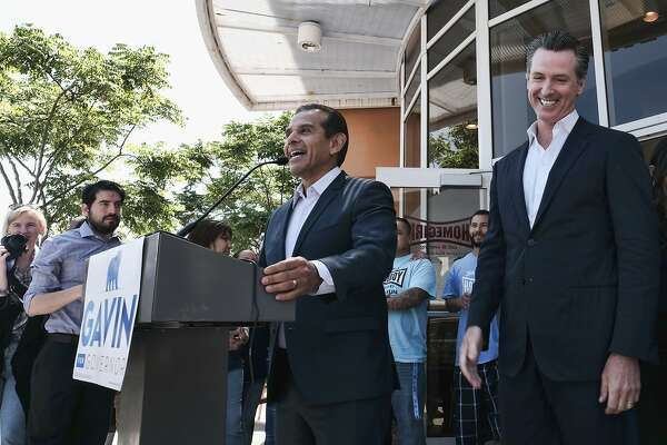 Lt. Gov. Gavin Newsom, right reacts to former Los Angeles Mayor Antonio Villaraigosa, center, during a news conference at t Homeboy Industries on Tuesday, June 19, 2018 in downtown Los Angeles. As rival Democratic candidates for governor, Newsom and Villaraigosa spent months talking about their differences. With the race behind them, they can't stop trading compliments as Newsom begins a fall campaign against Republican John Cox. (AP Photo/Richard Vogel)