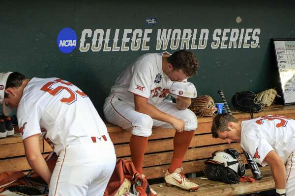 Texas pitcher Andy McGuire sits in the dugout between Turner Gauntt, right, and Sam Bertelson (55) following an NCAA College World Series baseball elimination game in Omaha, Neb., Tuesday, June 19, 2018. Florida won 6-1. (AP Photo/Nati Harnik)