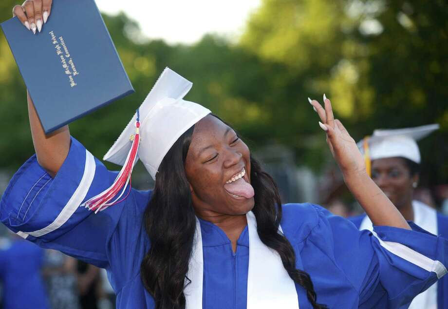 Above, Jessie Holmes celebrates the graduation of the class of 2018 during the Brien McMahon High School commencement ceremony Tuesday in Norwalk. At right, Photo: Erik Trautmann / Hearst Connecticut Media / Norwalk Hour