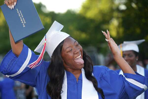 Above, Jessie Holmes celebrates the graduation of the class of 2018 during the Brien McMahon High School commencement ceremony Tuesday in Norwalk. At right,