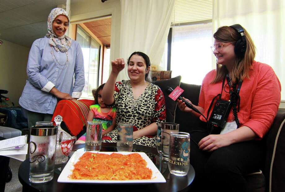 Zainab Al-Qaderi, a refugee chef from Iraq, seated in center, serves kanafeh, a Middle Eastern dessert, at her home in New Haven on Tuesday. With Zainab at left is Sumiya Khan of Sanctuary Kitchen at CitySeed, Zainab's daughter Ritaj, 4, and at right is WSHU reporter Cassandra Basler. Al-Qaderi will serve the dessert on Saturay at the World Refugee Day Festival. Photo: Christian Abraham / Hearst Connecticut Media / Connecticut Post