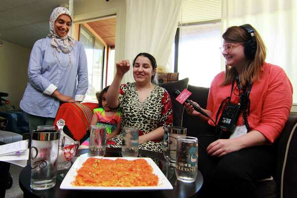 Zainab Al-Qaderi, a refugee chef from Iraq, seated in center, serves kanafeh, a Middle Eastern dessert, at her home in New Haven on Tuesday. With Zainab at left is Sumiya Khan of Sanctuary Kitchen at CitySeed, Zainab's daughter Ritaj, 4, and at right is WSHU reporter Cassandra Basler. Al-Qaderi will serve the dessert on Saturay at the World Refugee Day Festival.