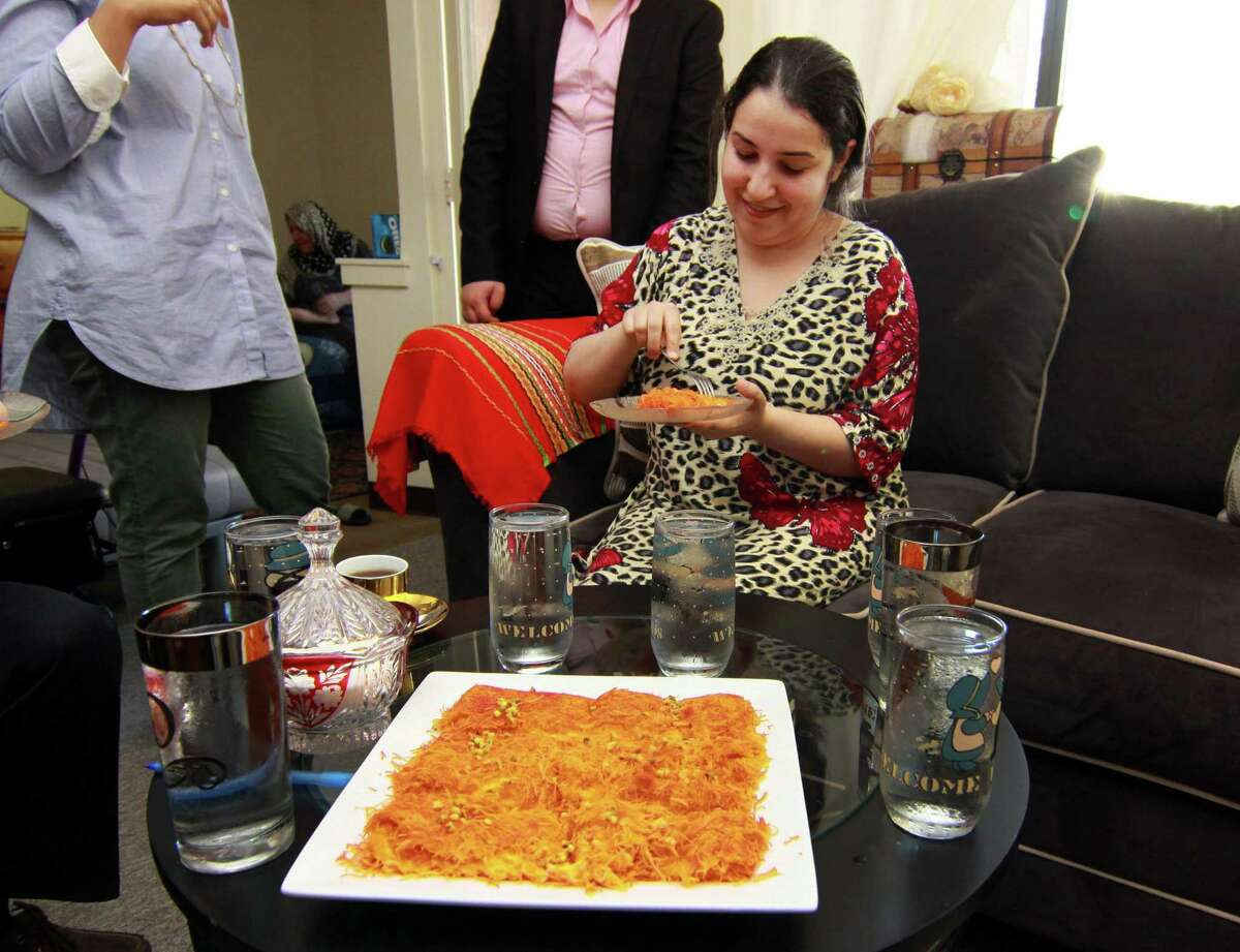 Zainab Al-Qaderi, a refugee chef from Iraq, tastes kanafeh, a Middle Eastern dessert which she made, at her home in New Haven on Tuesday. Al-Qaderi will serve the dessert on Saturday at the World Refugee Day Festival.