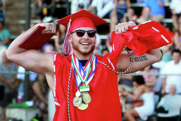 Graduate Tristan Pruzinsky flexes his muscles after ripping off the sleeves on his gown during Derby High School's 142nd Commencement in Derby, Conn., on Tuesday, June 19, 2018.