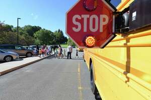 Children and parents practice crossing the street in front of a school bus during a bus safety event for parents and children entering kindergarten at the Rosendale Elementary School on Tuesday, Aug. 23, 2016, in Niskayuna, N.Y.   (Paul Buckowski / Times Union)