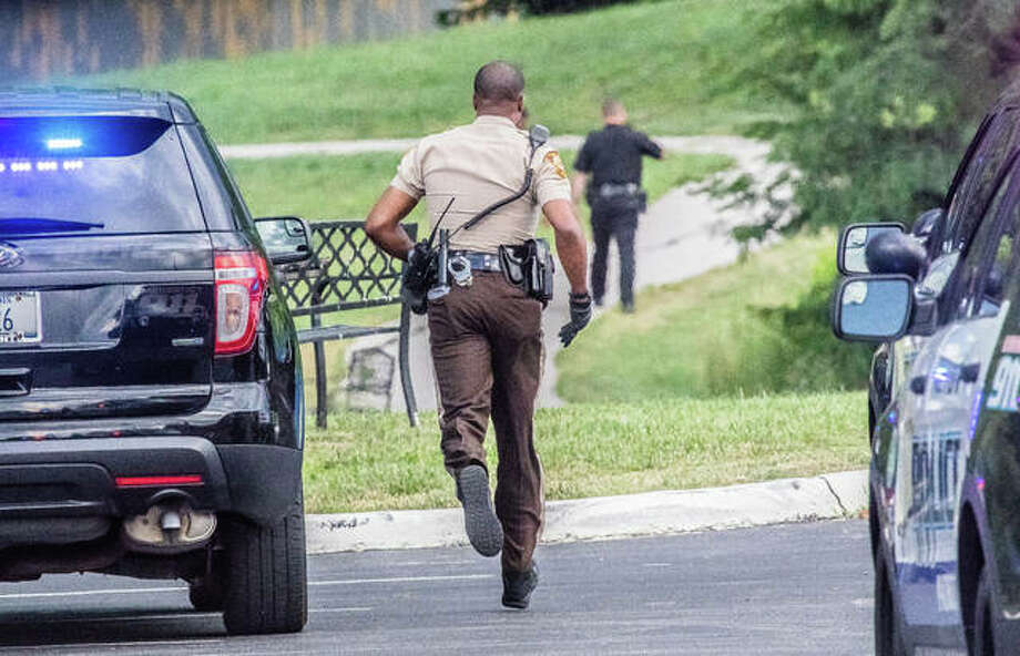 A St. Louis County Sheriff's Office deputy dodges between an audience of abandoned Alton Police Department squad cars after an armed carjacking in Alton led police on a chase that toured North County, ending a few hundred feet off of Old Jamestown Road, next to a pond and wooded area Tuesday evening. Photo:     Nathan Woodside | The Telegraph