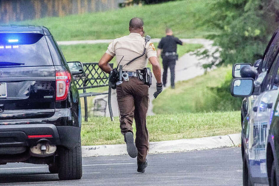 A St. Louis County Sheriff's Office deputy dodges between an audience of abandoned Alton Police Department squad cars after an armed carjacking in Alton led police on a chase that toured North County, ending a few hundred feet off of Old Jamestown Road, next to a pond and wooded area Tuesday evening.