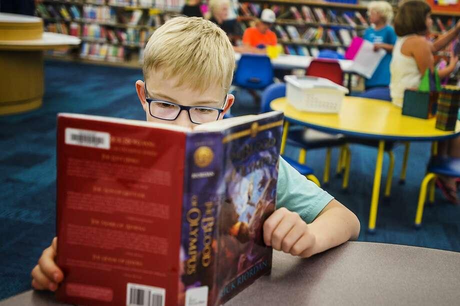 Midland resident Carter Gross, 9, reads a book during an open house for the newly renovated Youth Services section of the Grace A. Dow Memorial Library on Tuesday, June 19, 2018. (Katy Kildee/kkildee@mdn.net) Photo: (Katy Kildee/kkildee@mdn.net)