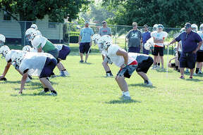 Jersey football coach Ric Johns, far right, watches his team go through drills during a summer workout session Tuesday at the Snyders Sports Complex in Jerseyville.