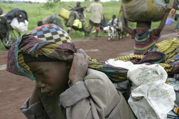 A young boy cries as he carries his belongings, as they flee fighting, near Kibumba, some 40 kilometers (25 miles) north of Goma in eastern Congo, Monday, Oct. 27, 2008. Thousands of refugees and soldiers are fleeing fighting in eastern Congo in what appears to be a major retreat of government forces being attacked by rebels of renegade Gen. Laurent Nkunda. (AP Photo/Karel Prinsloo)