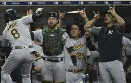 Third baseman Jed Lowrie is congratulated by teammates in the dugout after his two-run home run in the top of the 10th.
