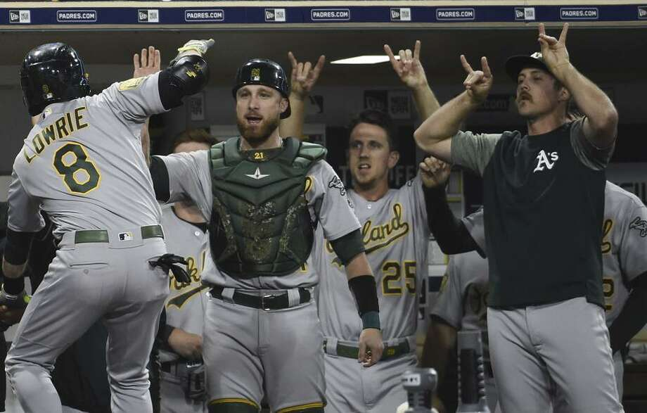 Third baseman Jed Lowrie is congratulated by teammates in the dugout after his two-run home run in the top of the 10th. Photo: Denis Poroy / Getty Images / 2018 Getty Images