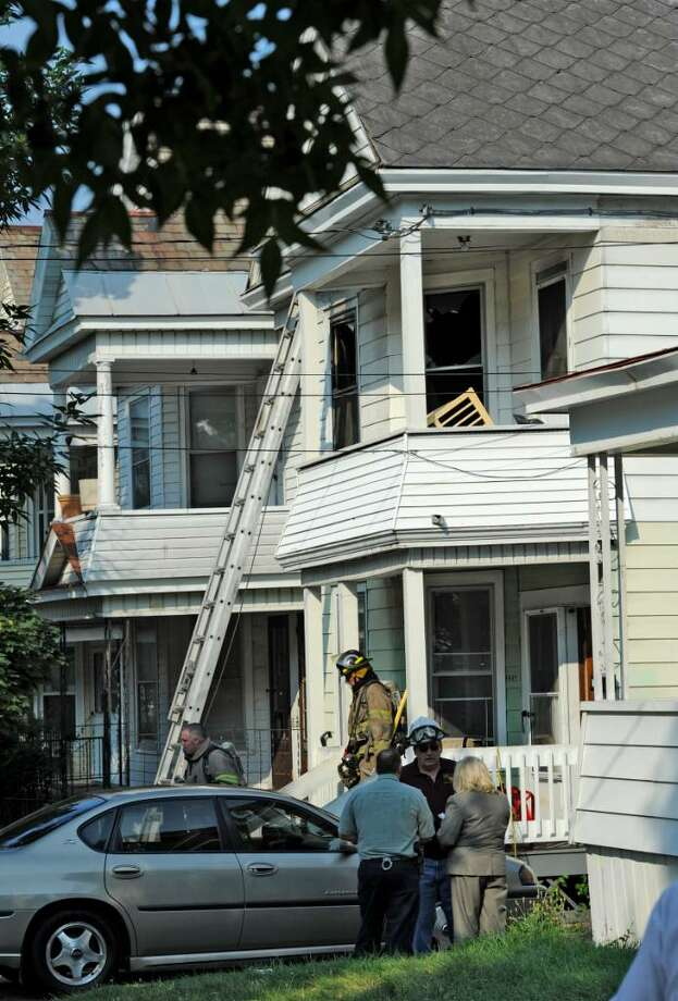 Schenectady firefighters and police at the scene of a house fire that left a woman and two children badly injured this morning on McClellen Street in Schenectady. (Skip Dickstein/Times Union) Photo: Skip Dickstein