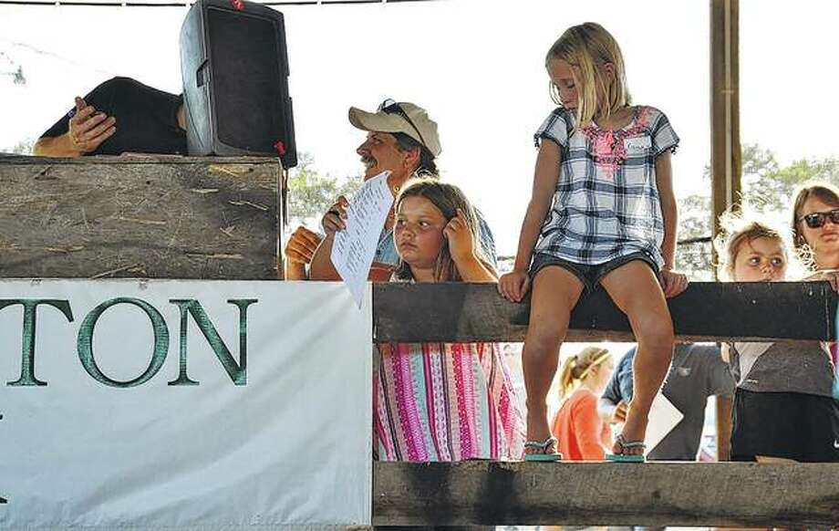 Two girls enjoy up-close seats at the Greene County 4-H livestock auction during the Greene County Fair. Several hundred people attended the auction. Fair festivities continue through Saturday. Grandstand entertainment includes tractor and truck pulls, a demolition derby and a mud drag.
