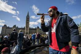 A resident smokes a large marijuana joint during the 420 Day festival on the lawns of Parliament Hill in Ottawa, Ontario, Canada, on April 20, 2018.