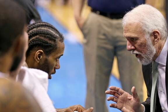 San Antonio Spurs' Kawhi Leonard talks with head coach Gregg Popovich on the bench during second half action of Game 6 in the Western Conference semifinals against the Oklahoma City Thunder Thursday May 12, 2016 at Chesapeake Energy Arena in Oklahoma City, Oklahoma. The Thunder won 113-99.