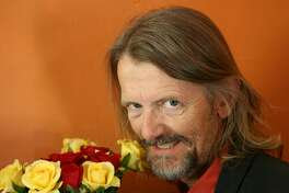 Weird looking mature man with bouquet of roses for woman he wants to seduce.