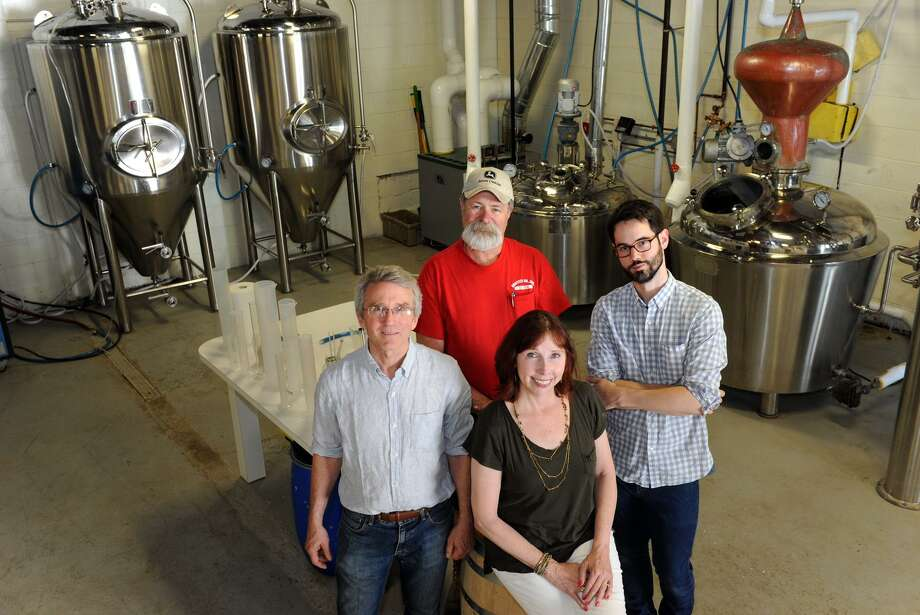 Robert and Bridget Schulten, front, and their business partners Gary Griffith and Neil Doocy at Asylum Distillery, in Bridgeport, Conn. June 2, 2016 Photo: Ned Gerard / Hearst Connecticut Media Group / Connecticut Post