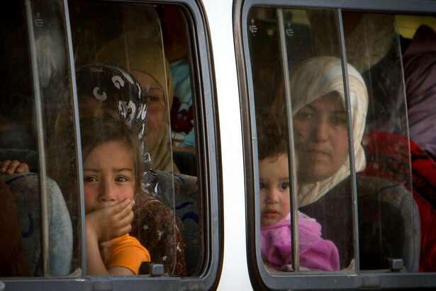 Syrian refugees arrive on a minibus at a refugee camp in Yayladagi, Turkey, Saturday, June 18, 2011 ferried shortly after crossing the Syria Turkey border.  Syrian troops backed by tanks and firing heavy machine guns swept into a village near the Turkish border Saturday, cutting food supplies for nearly 2,000 refugees who have so far refused to leave their country. Many of those men, women and children will have no choice but to flee across the frontier if troops descend on them.(AP Photo/Vadim Ghirda)