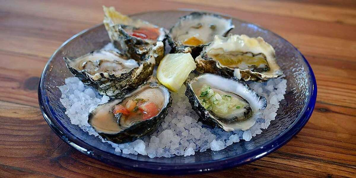 The First Mate Platter at Humboldt Bay Provisions features six raw bucksport oysters dressed with sauces.