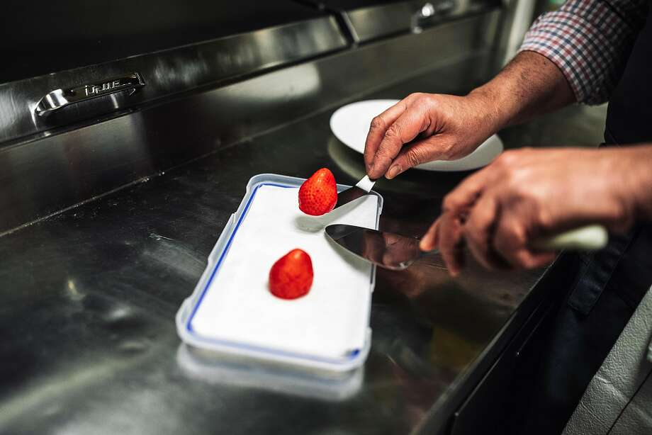 Bruno Chemel plates a dish of foie gras shaped like a strawberry and coated in berry gelee. Photo: Stephen Lam / Special To The Chronicle