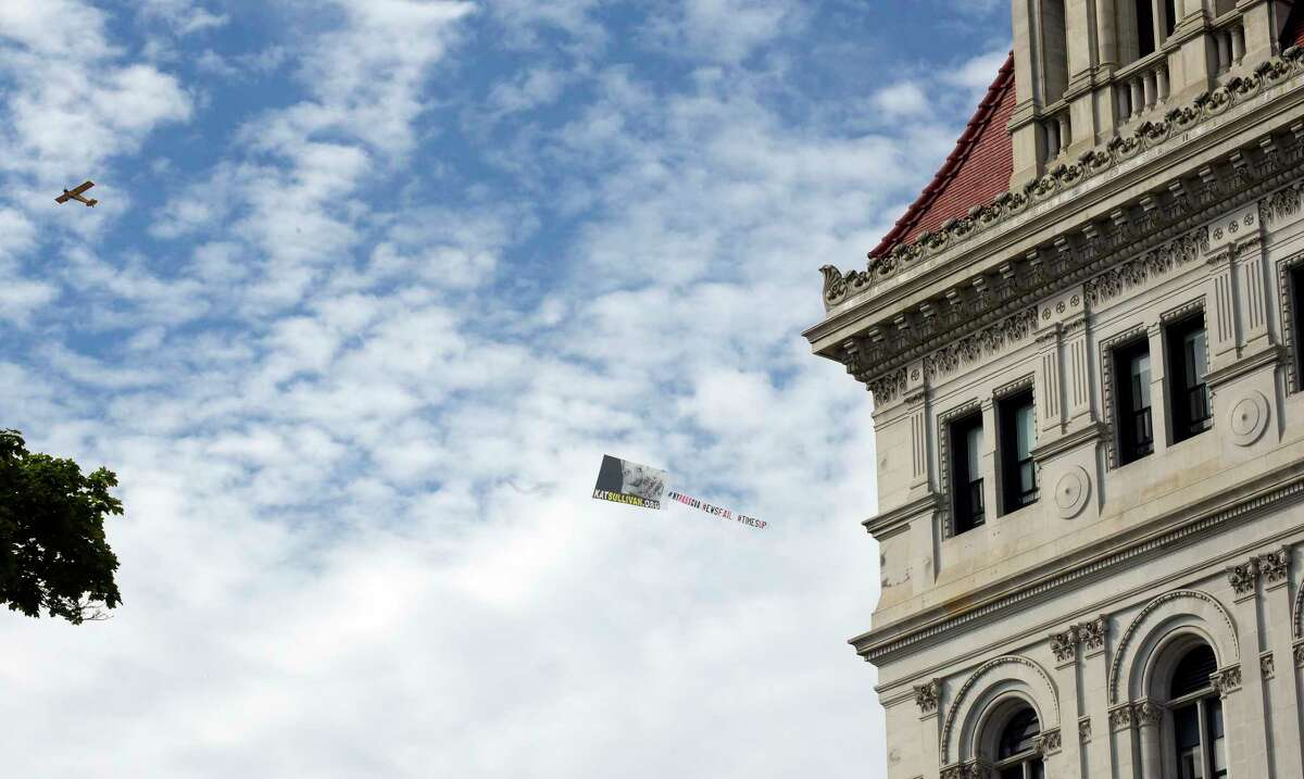An airplane pulling a sign for KatSullivan.org website, flies over the Capitol on Wednesday, June 20, 2018, in Albany, N.Y. Kat Sullivan is a survivor of child sex abuse, and she supports passage of the Child Victims Act. (Paul Buckowski/Times Union)
