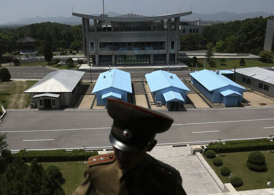 Buildings in South Korea are seen behind a North Korean soldier stationed at the Demilitarized Zone. Photo: Dita Alangkara / Associated Press