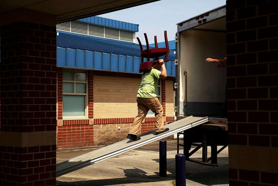 A mover loads furniture from a middle school onto a truck, in Williamston, N.C. The school is joining with the local high school because there aren't enough students to keep both open. Photo: Travis Dove / New York Times