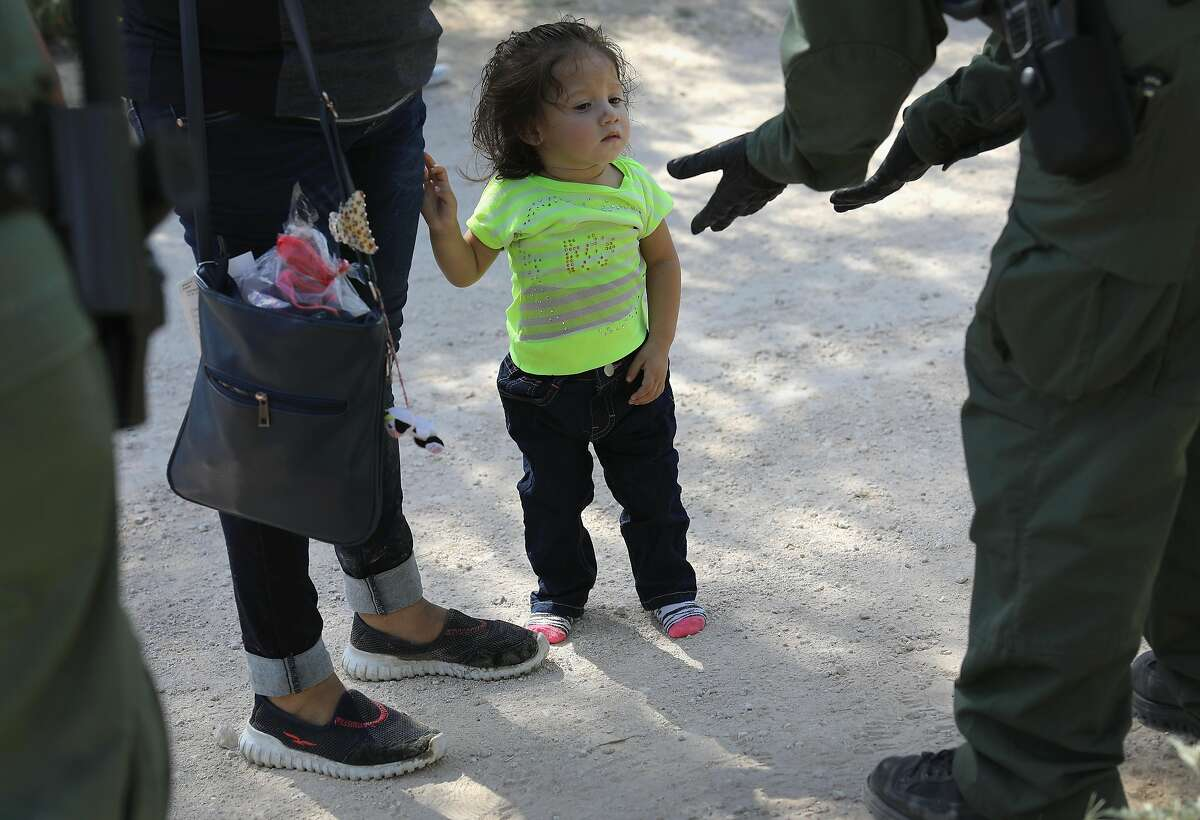 U.S. Border Patrol agents take Central American asylum seekers into custody on June 12 near McAllen. The number of unaccompanied children in migrant shelters reached a record of more than 14,000 in November, including more than 5,600 in Texas. More children are not coming here, but they are being detained for much longer before being released to adult sponsors, usually family.