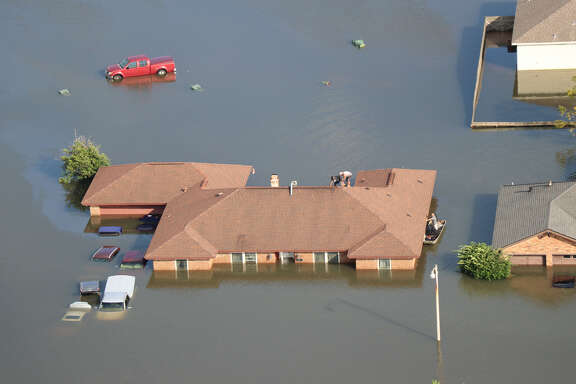 Residents of Beaumont, Texas, use a boat to get to the roof of their flooded house on Aug. 31, 2017, after the flooding caused by Hurricane Harvey. 