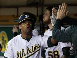 Oakland Athletics' Khris Davis is high-fived in the dugout after scoring on a double by Matt Chapman during the sixth inning of a baseball game against the Kansas City Royals on Thursday, June 7, 2018, in Oakland, Calif. (AP Photo/Marcio Jose Sanchez)