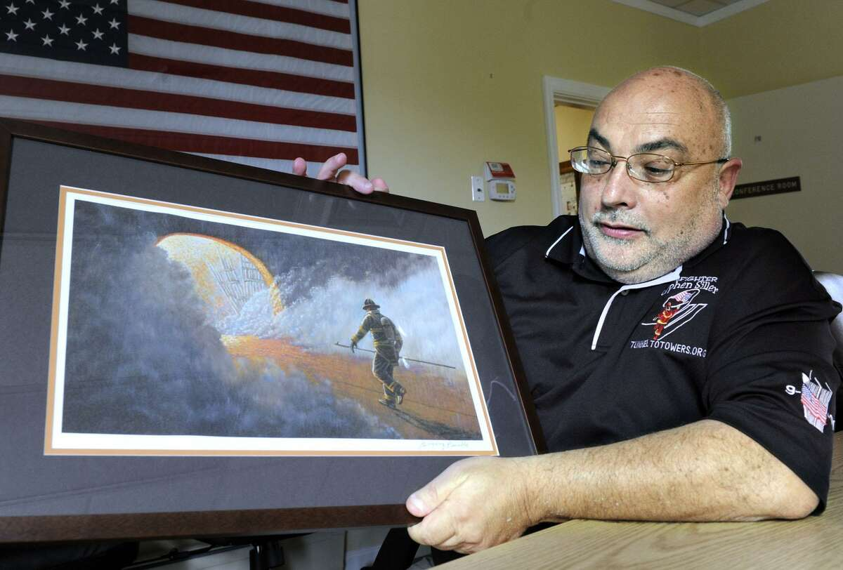New Fairfield First Selectman John Hodge holds a picture that depicts his cousin, Stephen Siller, a New York City firefighter, who died on Sept. 11.