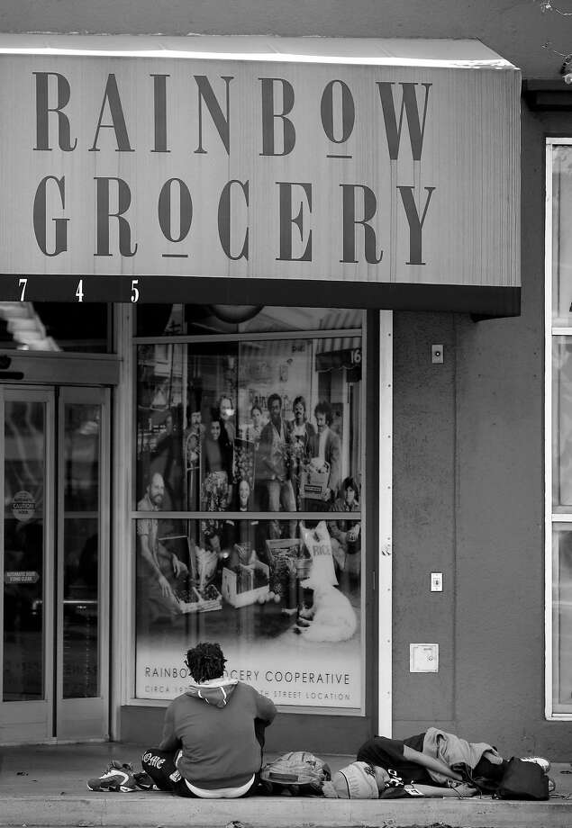 People sit and lie on the sidewalk outside Rainbow Grocery. Photo: Lea Suzuki / The Chronicle