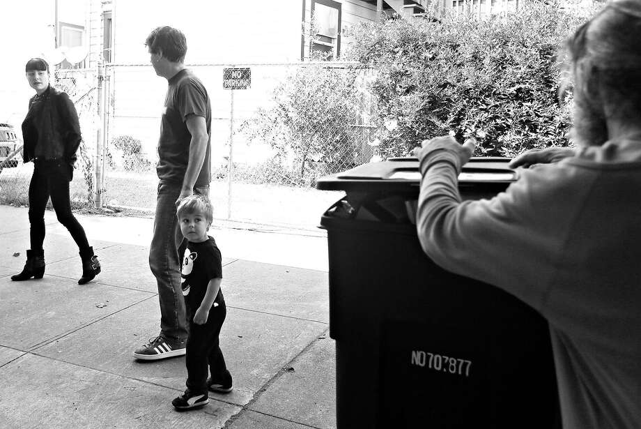 Ernst Schoen-Rene, his wife, Jill, and their son, Laszlo walk along 13th Street as a man looks in a garbage bin. Photo: Lea Suzuki / The Chronicle
