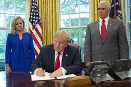 President Donald Trump signs an executive order to keep families together at the border, but says that the 'zero-tolerance' prosecution policy will continue, during an event in the Oval Office of the White House in Washington, Wednesday, June 20, 2018. Standing behind Trump are Homeland Security Secretary Kirstjen Nielsen, left, and Vice President Mike Pence. (AP Photo/Pablo Martinez Monsivais)