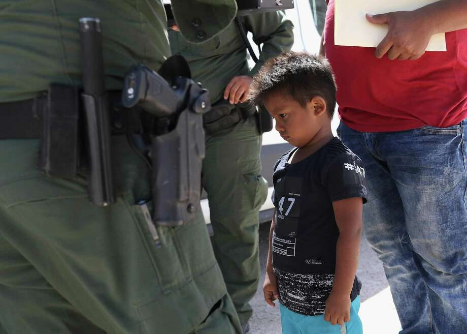 A boy and father from Honduras are taken into custody by U.S. Border Patrol agents near the U.S.-Mexico Border on June 12, 2018 near Mission, Texas. The asylum seekers were then sent to a U.S. Customs and Border Protection (CBP) processing center for possible separation. Photo: John Moore / Getty Images, Staff / John Moore / Getty Images / 2018 Getty Images